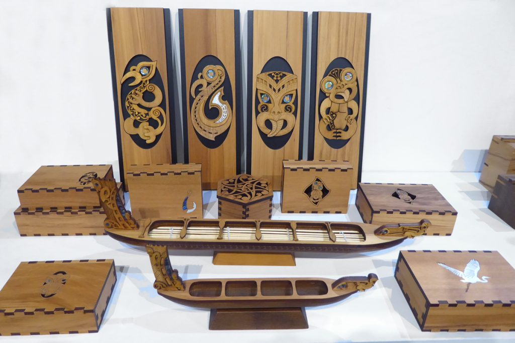 Wooden panels, waka and boxes with maori designs by Aeon Giftware