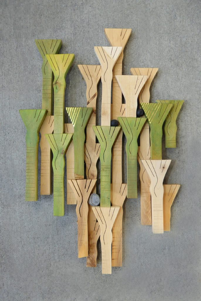 Wooden carved wall hanging of a grove of Nikau trees by Peter Radley